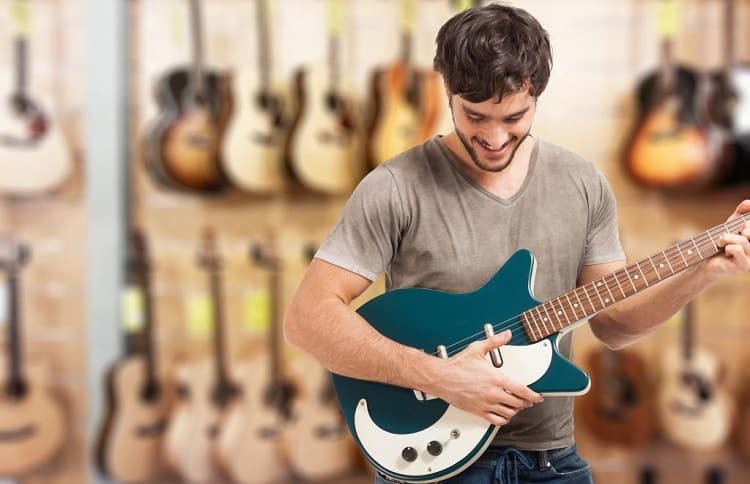 young man play on electric guitar